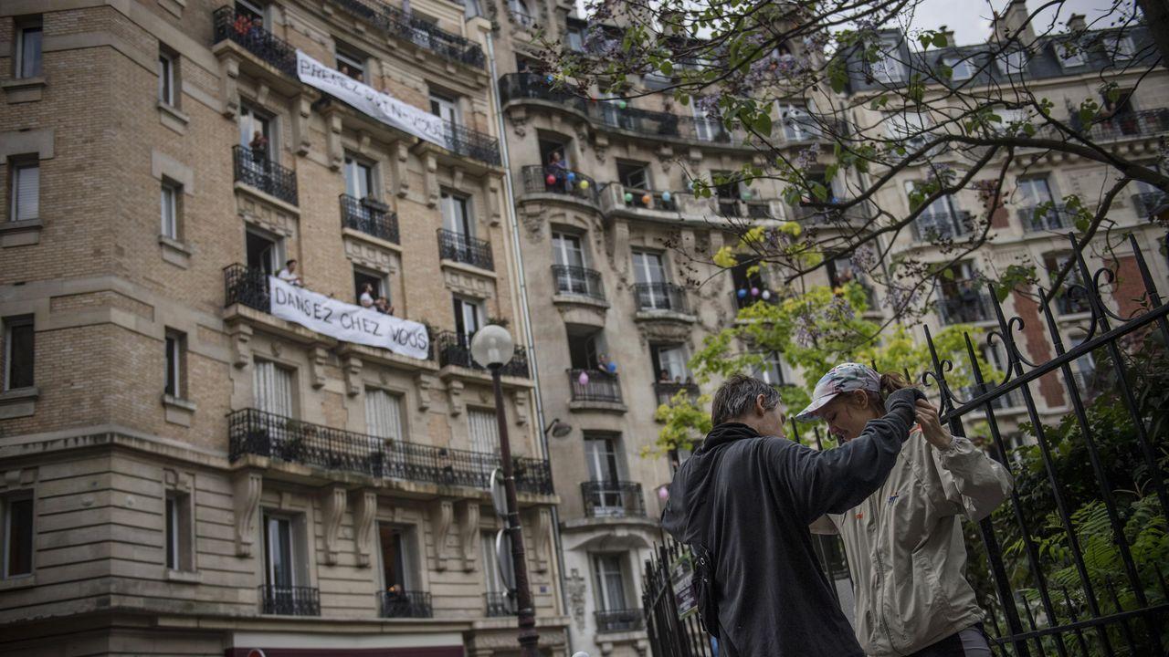 Una pareja baila en París al ritmo de un DJ que pincha en una ventana