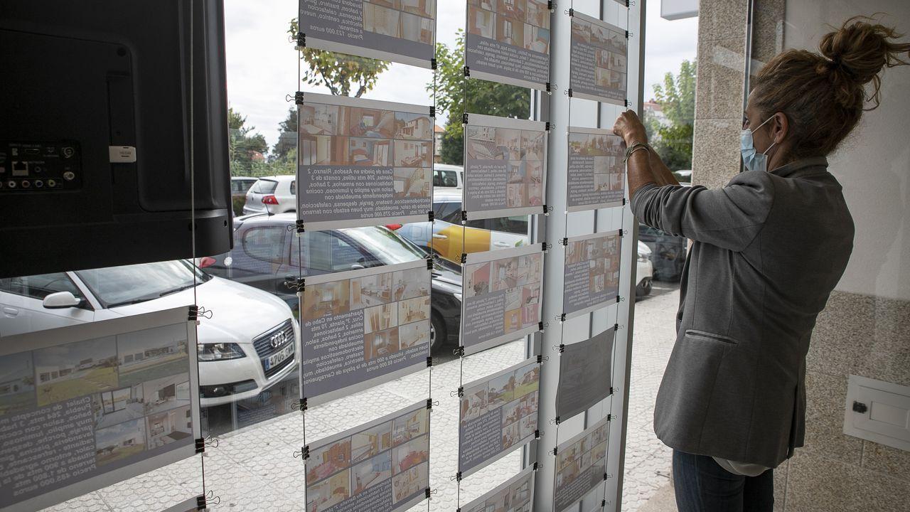 La responsable de una inmobiliaria coloca carteles de anuncio en su escaparate