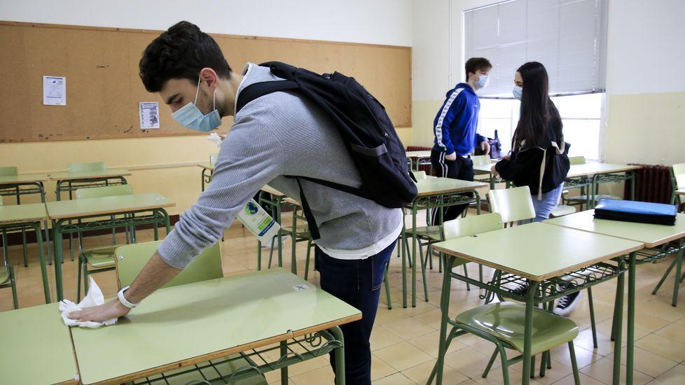 Un alumno desinfecta su mesa y silla en el IES Ollos Grandes de Lugo en el regreso a las aulas