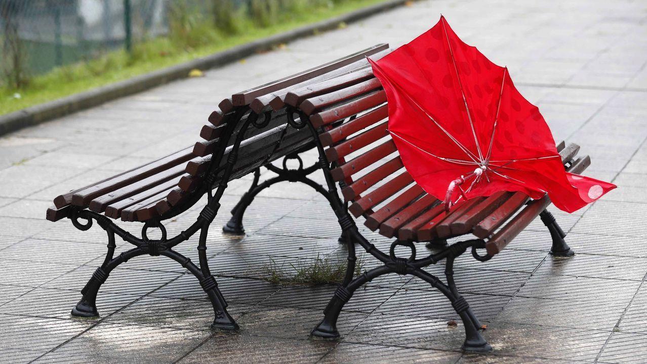 Un paraguas abandonado en un banco de un parque de Oviedo, en pleno temporal