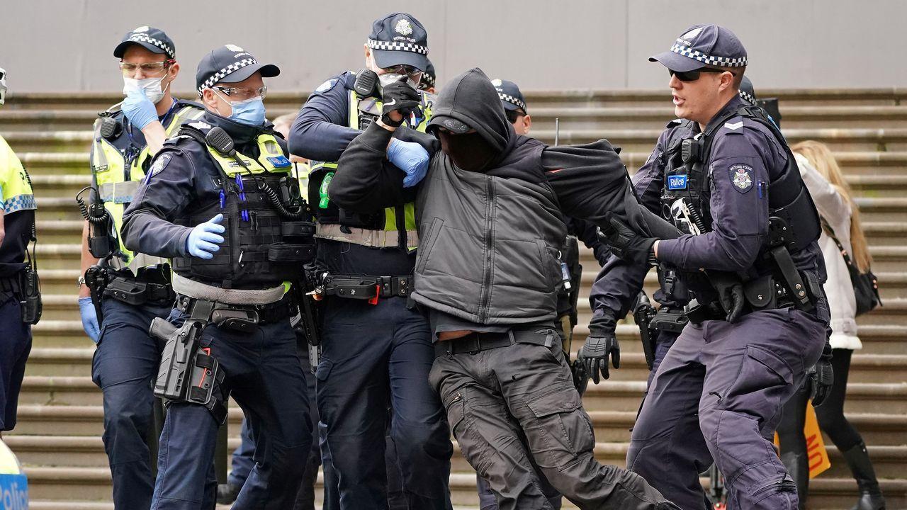 Oficiales de policía detienen a un manifestante que se opone a las medidas de confinamiento en Melbourne