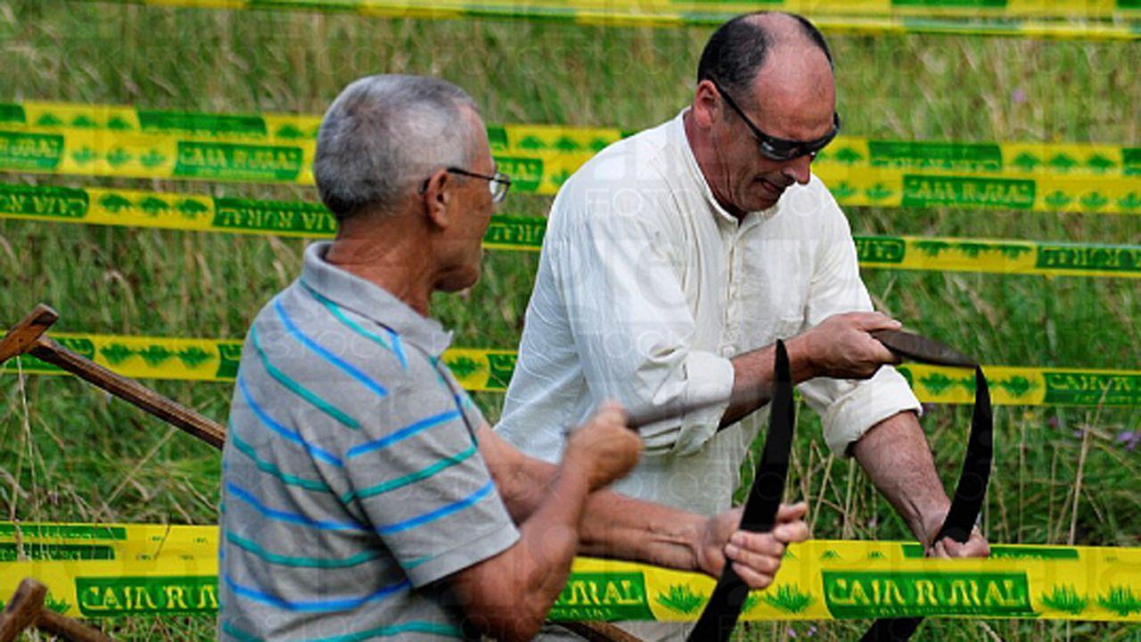 Alfonso Díaz afilando su guadaña junto a otro segador
