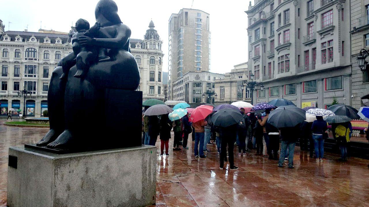 La predicción del tiempo para las próximas horas.Un grupo de personas con paraguas en La Escandalera de Oviedo