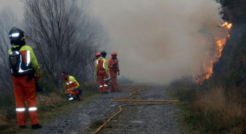 Operarios intentando apagar el fuego en Vegadeo, ayer en su tercer día.