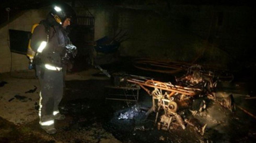 Un bombero ante uno de los enseres afectados por el incendio en El Castrillón (Laviana)