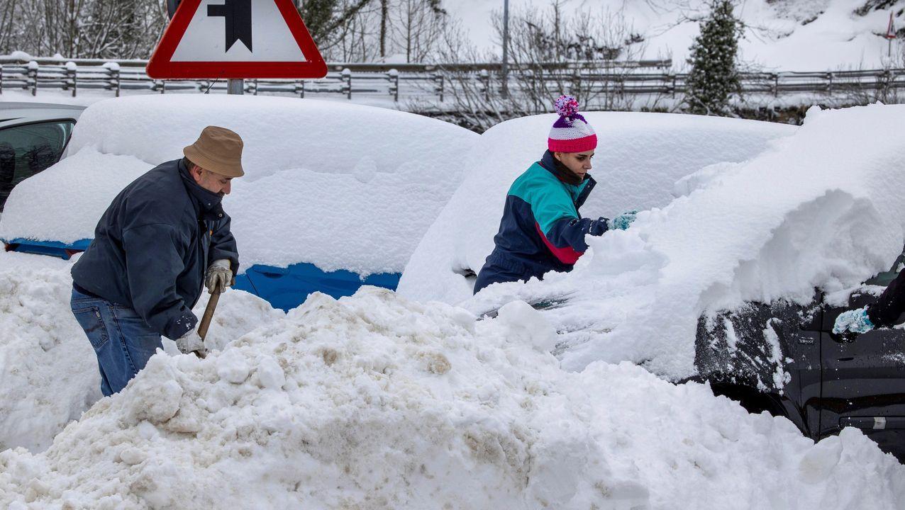 Cultivode cáñamo industrial enAsturias.unos vecinos tratan de quitar la nieve de sus vehiculos en el pueblo de Pajares