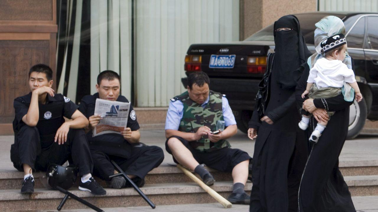Mujeres de la etnia uigur pasan por delante de policías chinos en la ciudad de Urumqi, en la provincia de Xinjiang