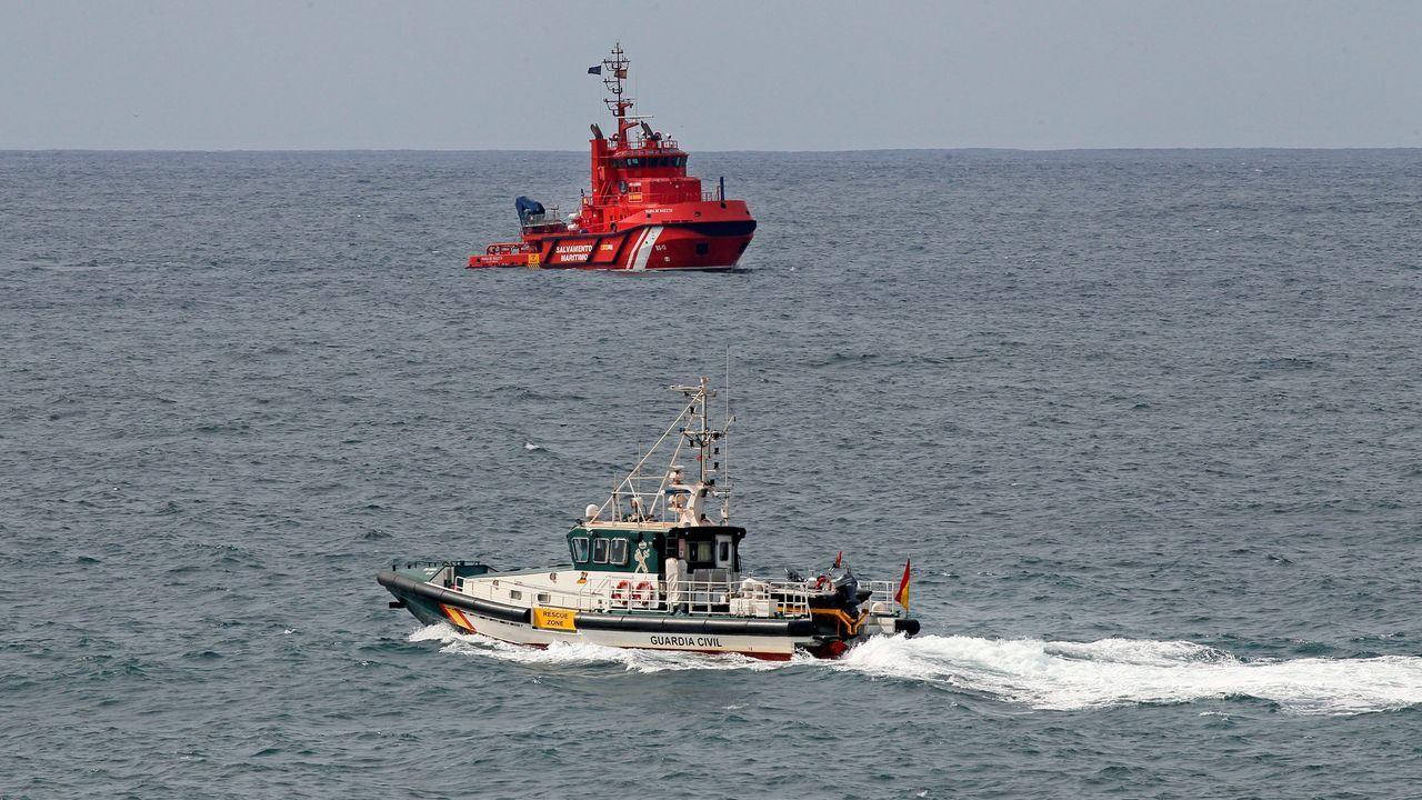 Un barco de la Cruz Roja y otro de la Guardia Civil rastrean la playa de Arnao en el municipio asturiano de Castrillón, durante la búsqueda de la mujer de 35 años que cayó al agua mientras pescaba