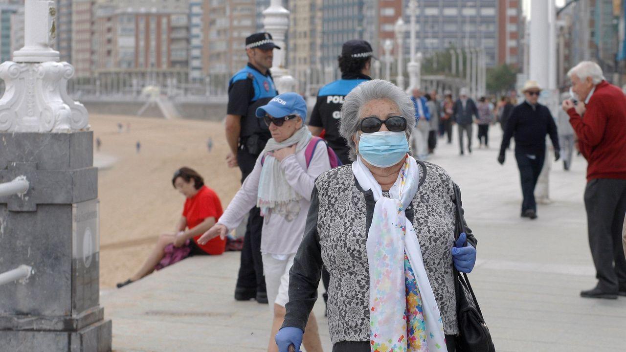 Primer domingo de fase 1 en Galicia: nadie se queda en casa.Personas mayores de 70 años pasean por el Muro de San Lorenzo, en Gijón