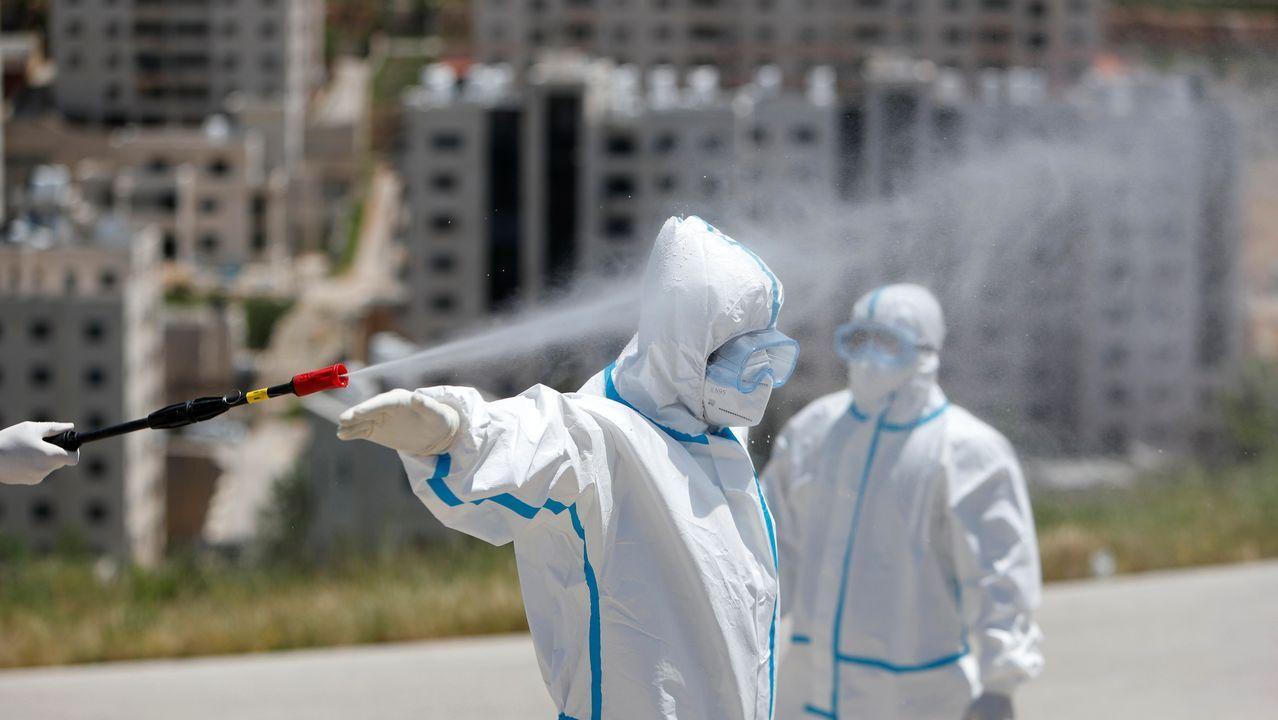 Un sanitario palestino es rociado con desinfectante durante un simulacro