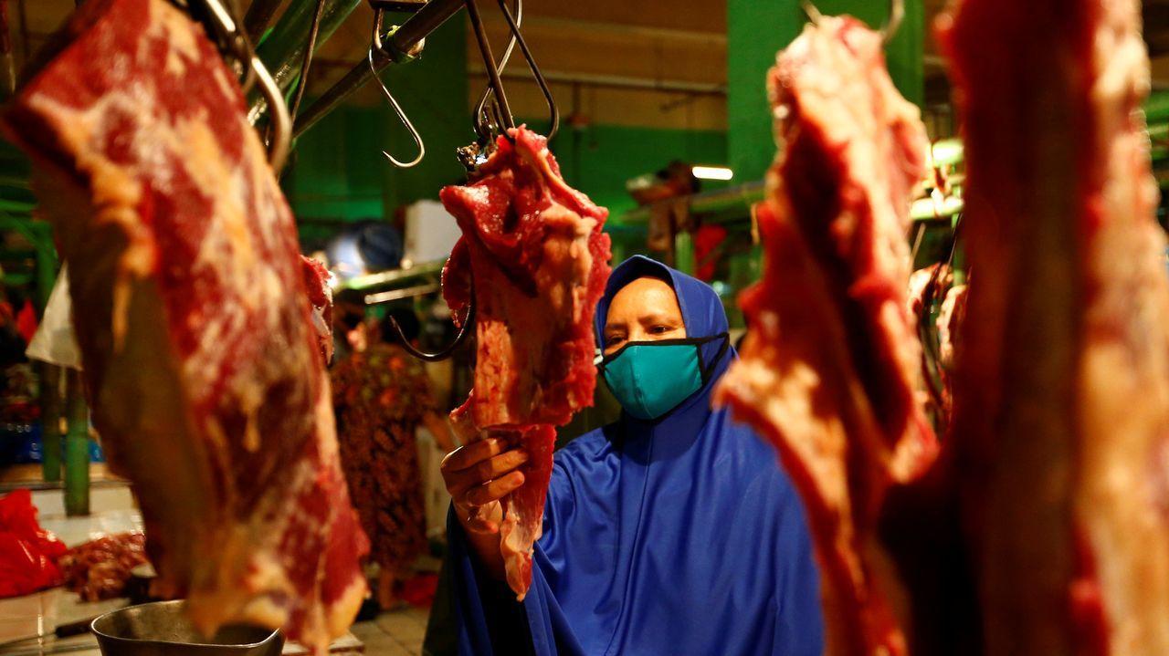 Una mujer lleva mascarilla mientras hace la compra en un mercado indonesio