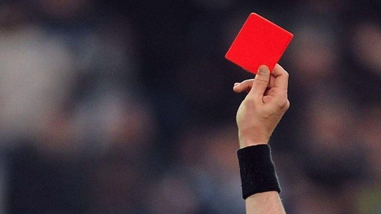 Un árbitro muestra una tarjeta roja