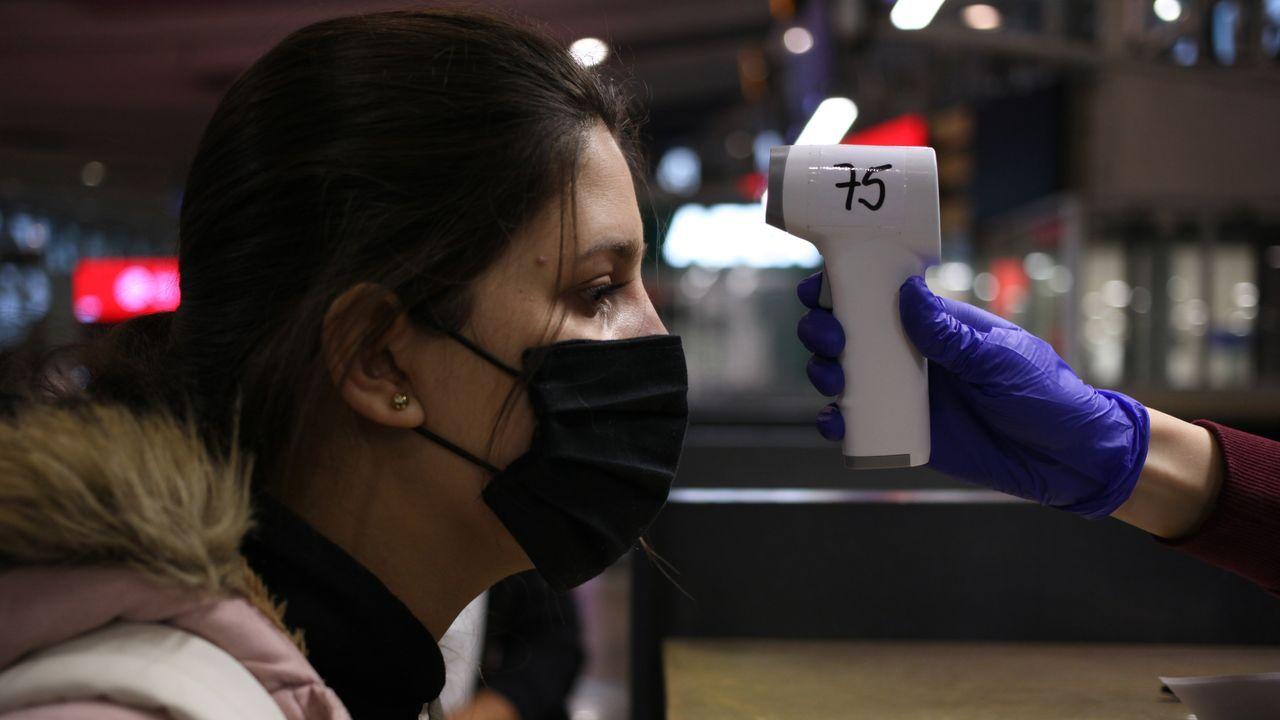 Imágenes de la pandemia en el mundo.Toma de temperatura a una ciudadana colombiana antes de coger un avión en el aeropuerto de Santiago, ayer en la capital chilena