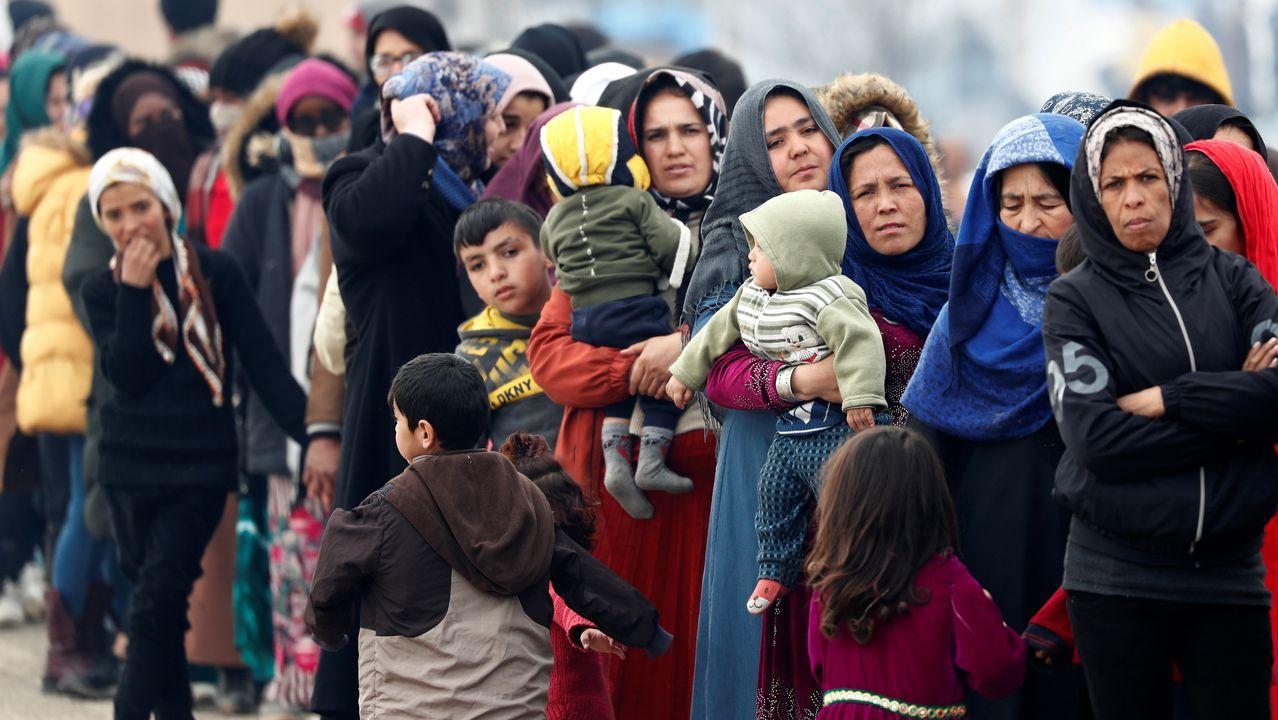Mujeres y niños hacen cola para recibir comida en el paso turco de Pazarkule,  donde se hacinan varios miles de migrantes