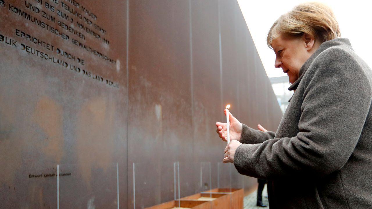 Merkel enciende una vela en la placa que recuerda a las víctimas del regimen comunista