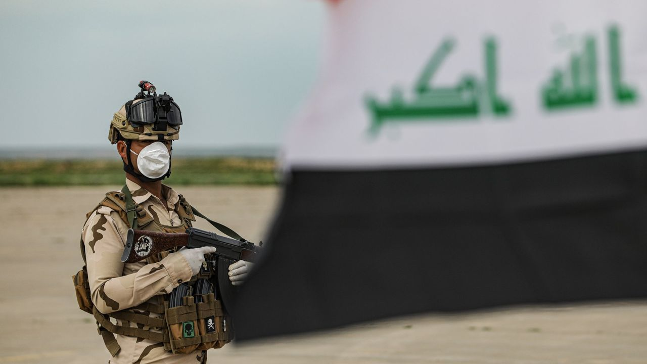 Bronco enfrentamiento en el Congreso entre el Gobierno y la oposición.Un miembro de las fuerzas de seguridad iraquíes vigila un puesto de control
