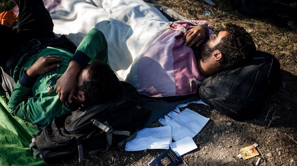 Un grupo de inmigrantes y refugiados descansan al lado de una via de ferrocarril en Serbia