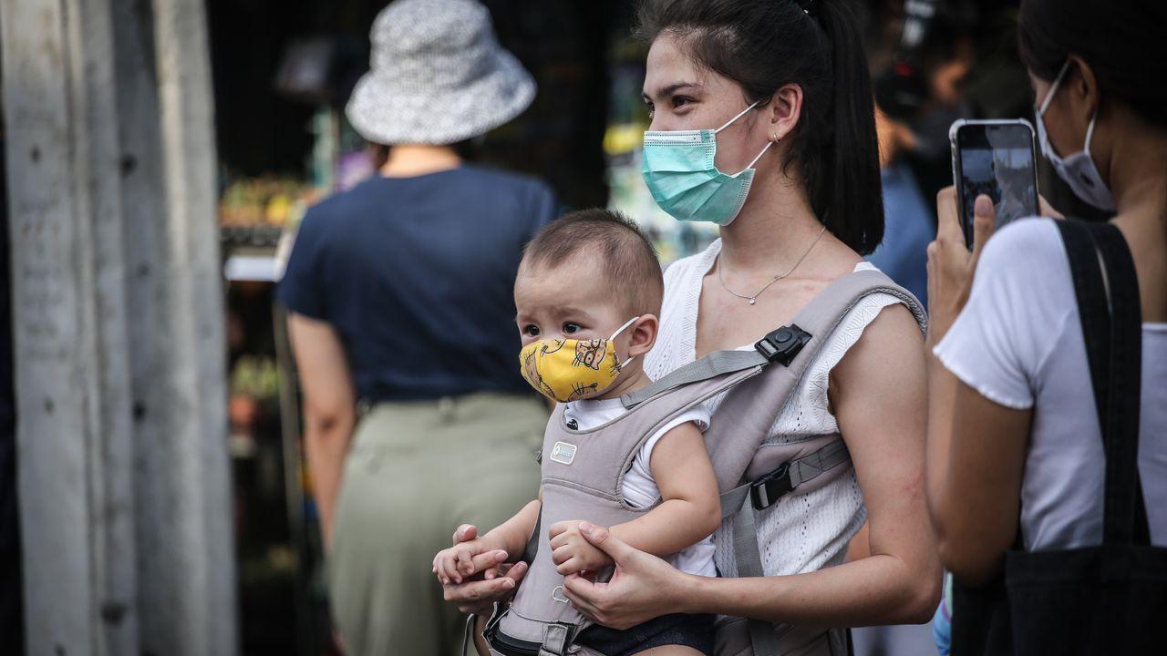 En Tailandia, una madre y su hijo, ambos con mascarilla, acuden a un mercado