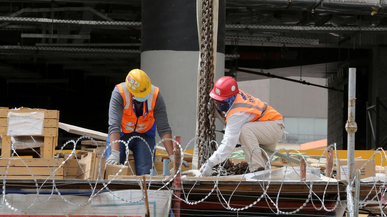 Trabajadores de la construcción usan mascarillas en un edificio en obras en Riad, Arabia Saudí