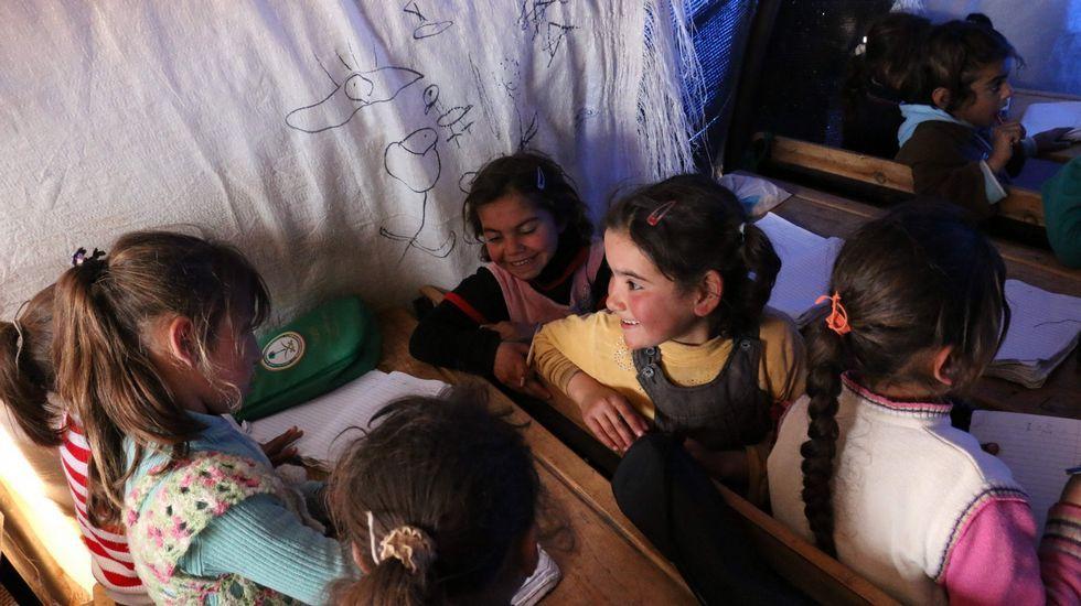 Nenas sirias desprazadas nun campamento para refuxiados asisten a clase