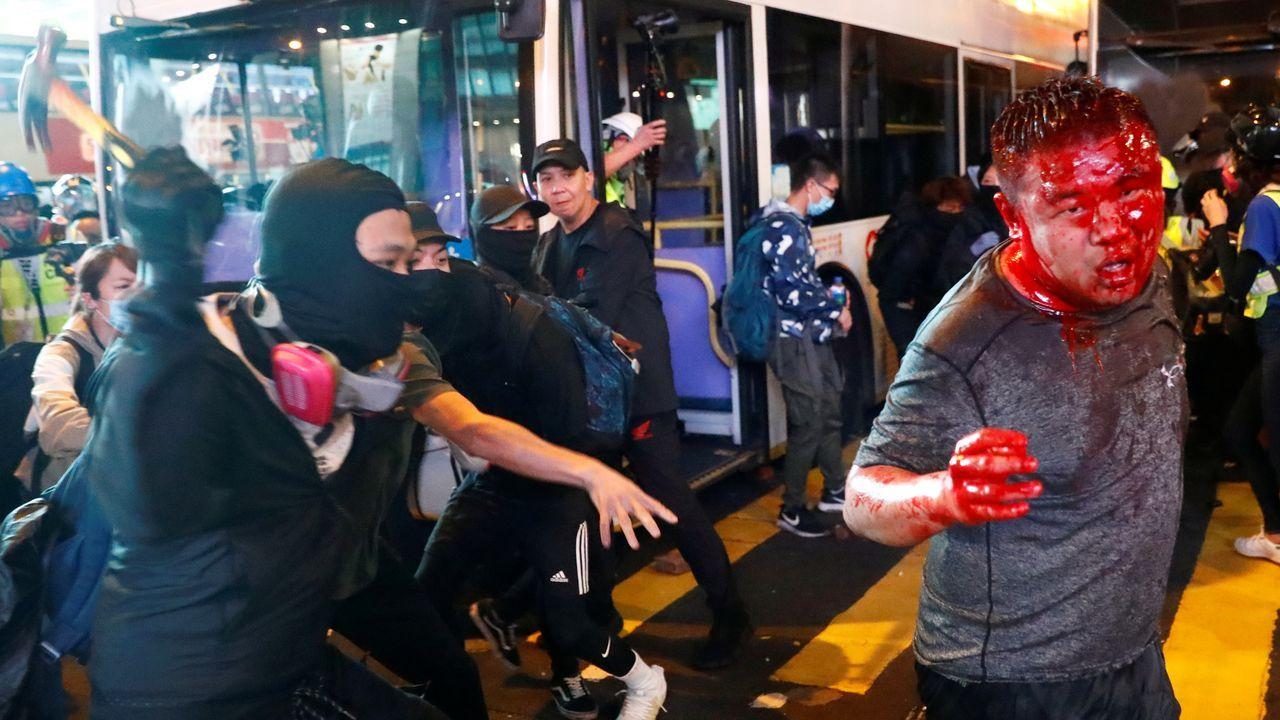 Un manifestante es atacando con un martillo por grupos prochinos