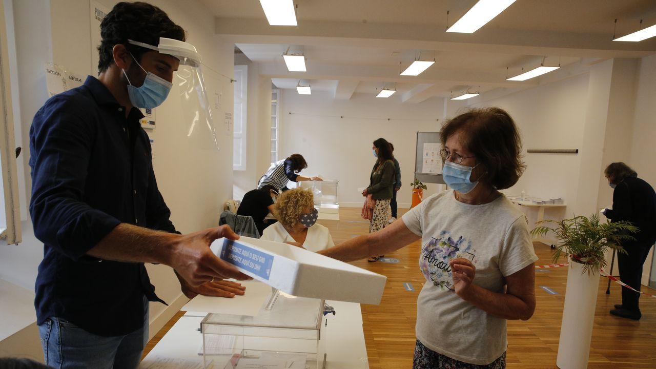 Una electora deposita su DNI en una bandeja en el Centro cívico Cidade Vella de A Coruña
