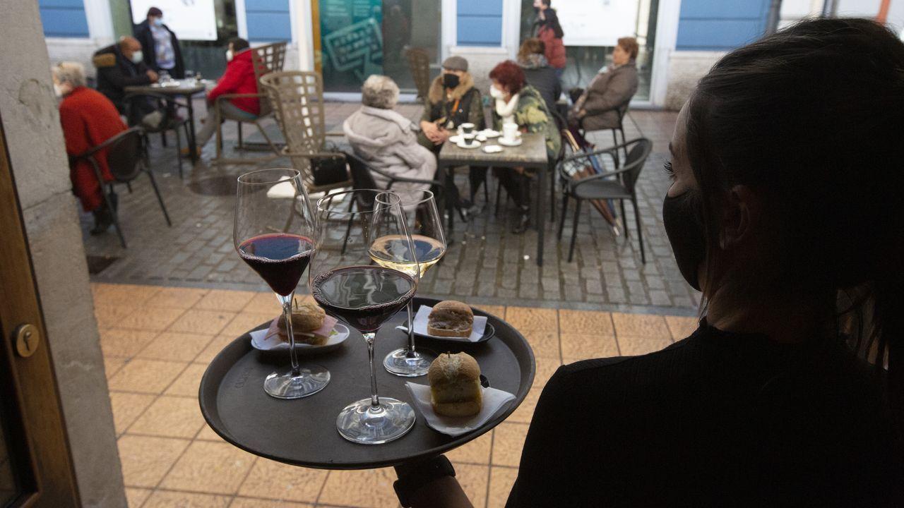 Una camarera se dispone a servir en una terraza de un restaurante de Avilés