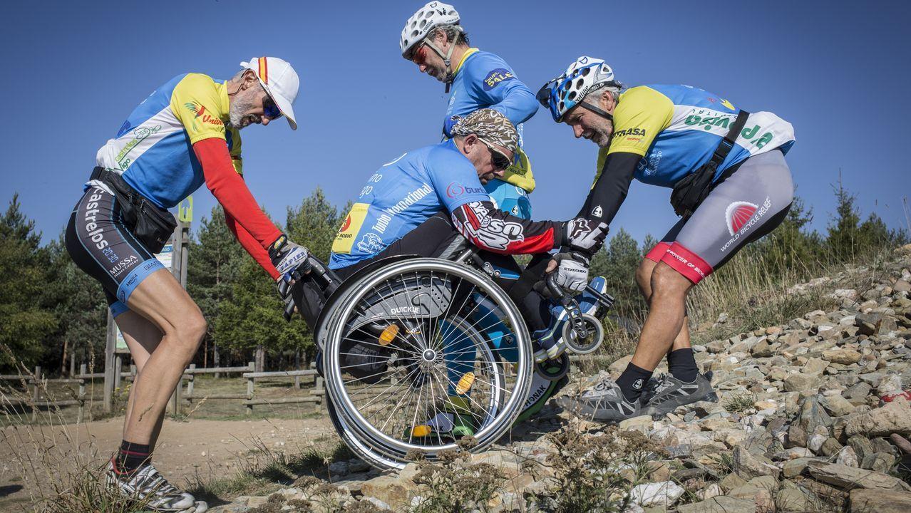 Álvaro y Jorge Pino ayudan a Suso Valverde a subir a la Cruz de Ferro en su handbike