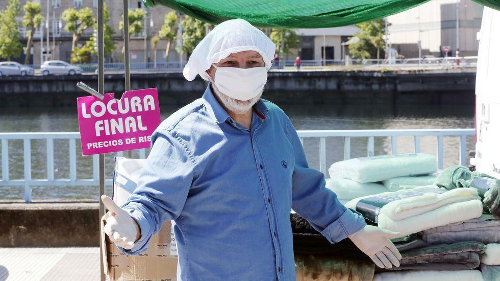 Reapertura de la feria de los sabados con nuevas medidas de seguridad. Un vendedor se protege del coronavirus con una mascarilla y una braga de algodón en la cabeza