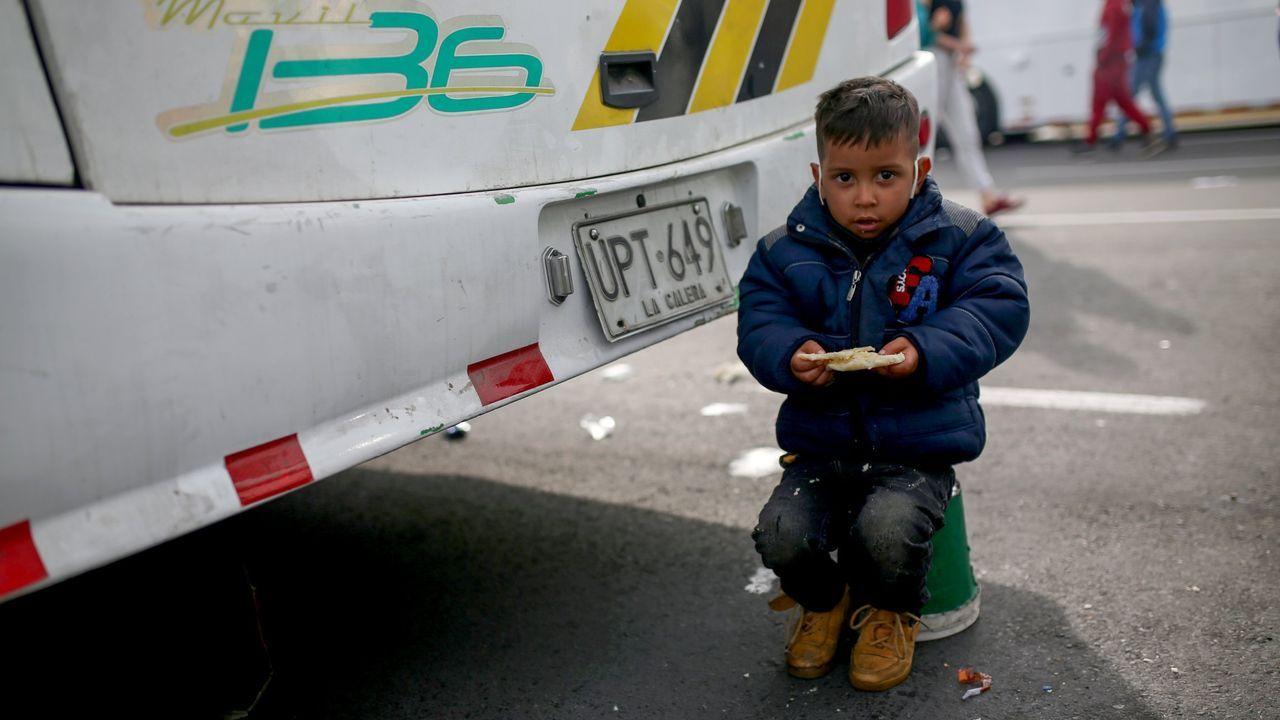 Un niño migrante venezolano come durante la parada del autobús que los lleva de regreso a su país
