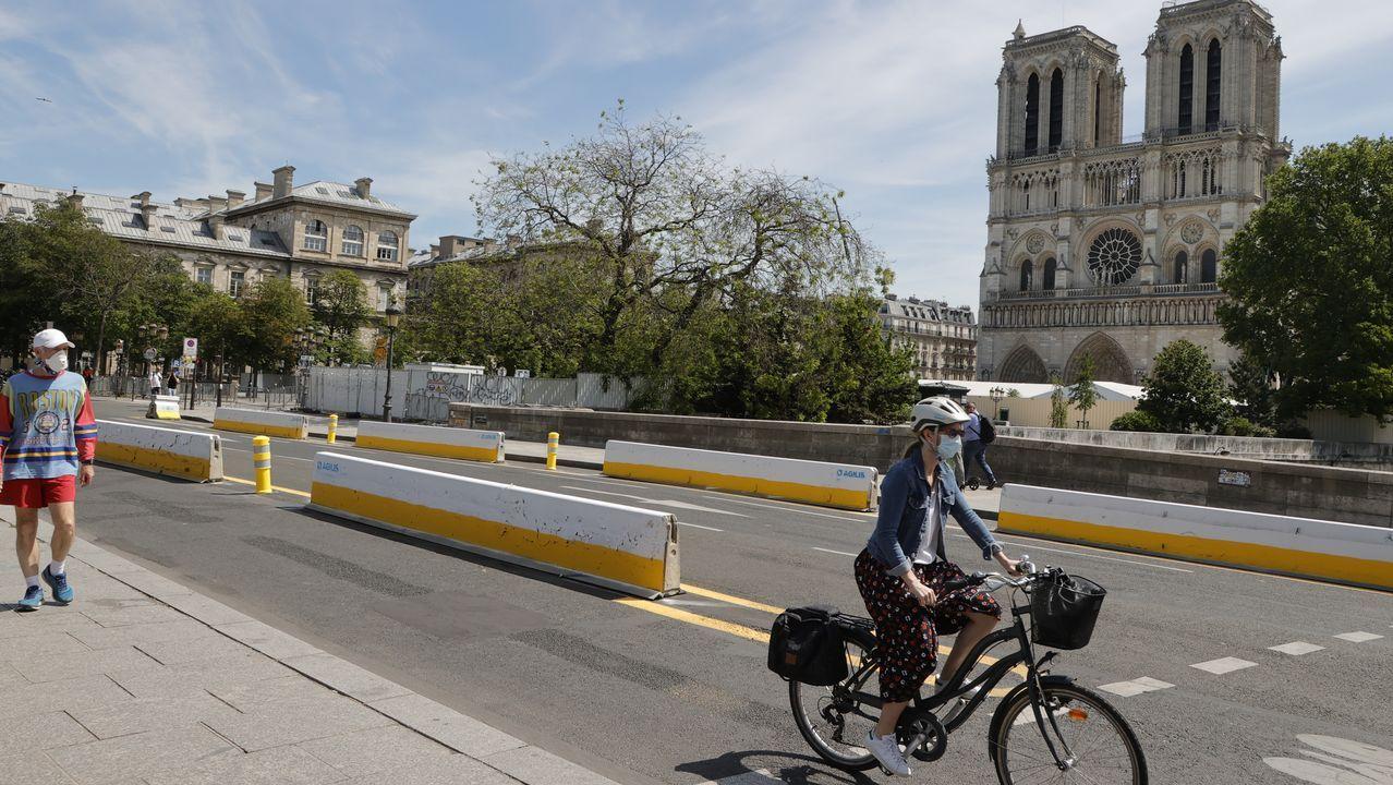 Una ciclista pasa al lado de la catedral de Notre Dame, y utiliza uno de los nuevos carriles específicos que la alcaldesa ha habilitado para los desplazamientos por la ciudad