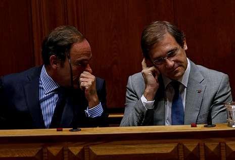 Passos Coelho charla con el viceprimera ministro Portas, en una sesión en el Parlamento.