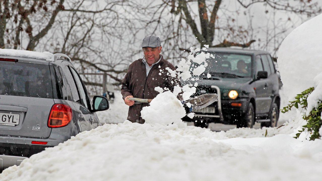 Temperaturas bajo mínimos en Galicia.un vecino del pueblo de Pajares trata de sacar su coche tras la nevada