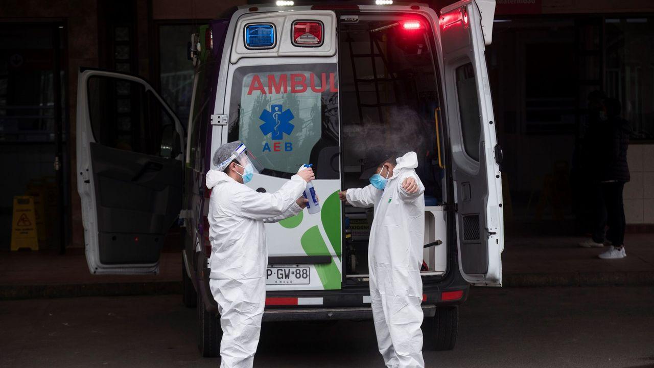 Trabajadores sanitarios se desinfectan en la entrada del servicio de urgencias del Hospital San José en Santiago, Chile