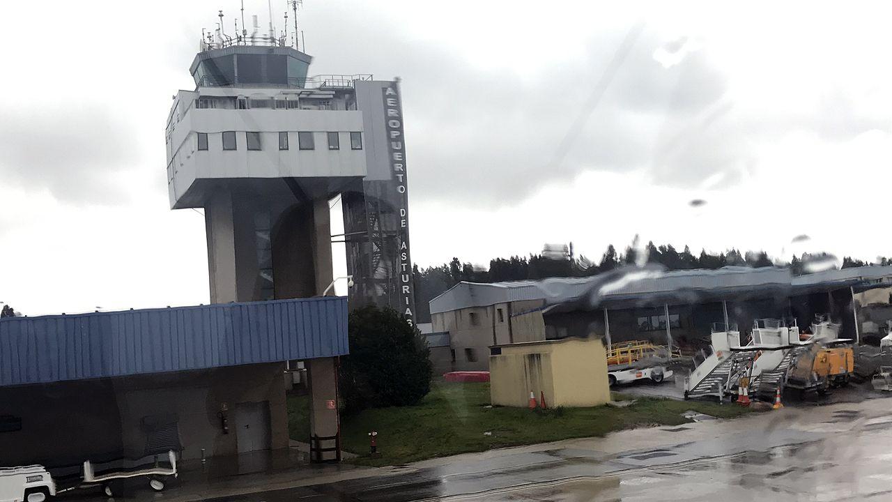 Un grupo de pasajeros consulta los vuelos en el Aeropuerto de Asturias.La torre de control del Aeropuerto de Asturias detrás de un cristal mojado por la lluvia