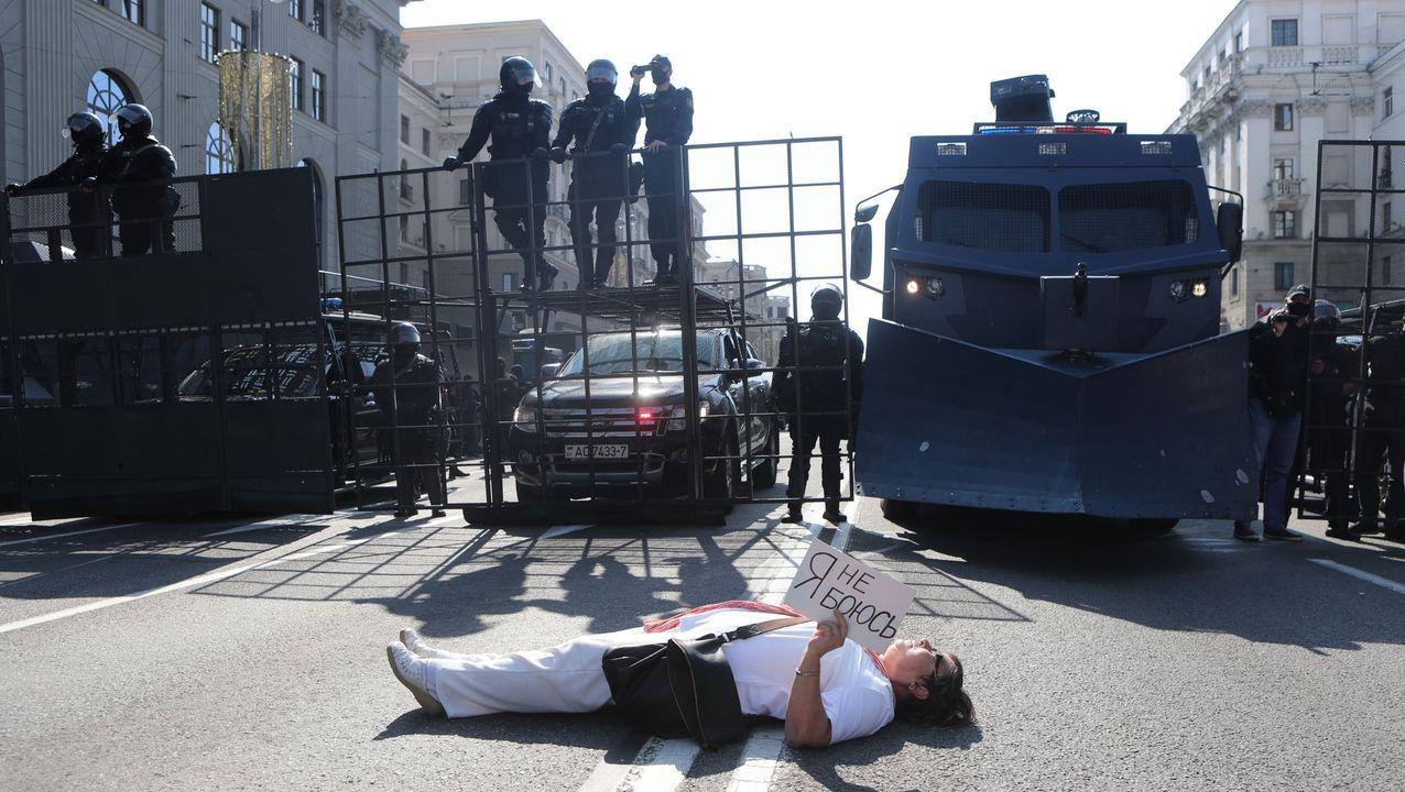 Una mujer yace en el suelo y sostiene el cartel «No tengo miedo» frente a la policía durante la manifestación del domingo en Minsk