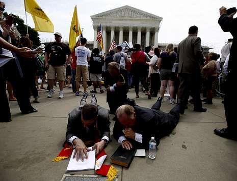 Líderes religiosos rezan sobre una Biblia tras conocer el veredicto del Supremo.