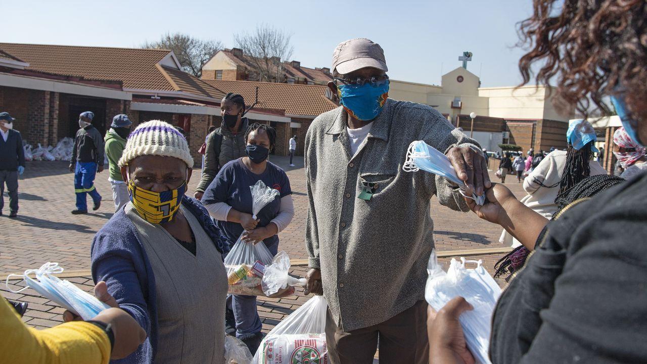 Ciudadanos con mascarilla reciben ayuda durante la pandemia en Soweto, Sudáfrica
