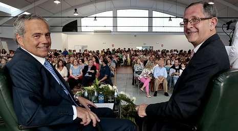 El Oncólogo Alfonso Mariño y el alcalde de Carballo, Evencio Ferrero, ante un auditorio en el Mercado abarrotado de público.
