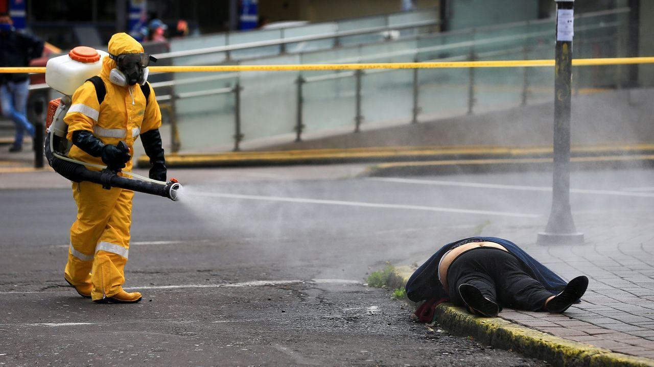 Un trabajador desinfecta a una persona que yace en el suelo, desplomada, en Quito