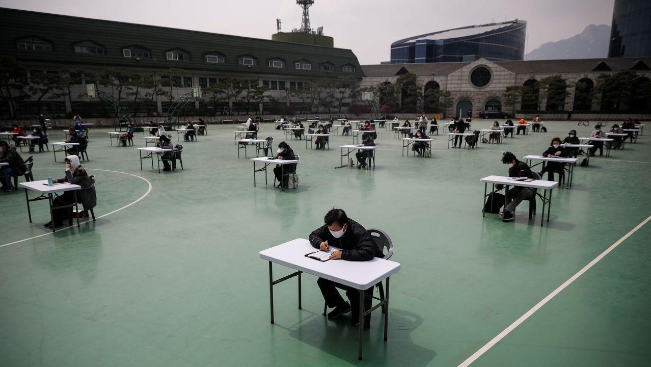 Exámenes al aire libre en Corea del Sur.Surcoreanos observan en la televisión una información sobre Kim Jong