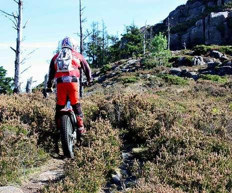 Un aficionado, en la subida al Pindo, con una moto de trial.