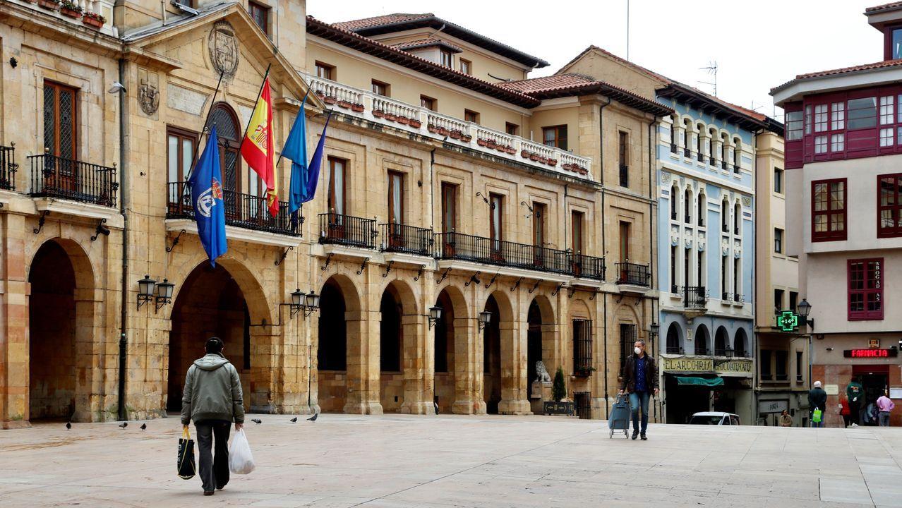 Personas pasean este martes por la plaza de Ayuntamiento de Oviedo durante una nueva jornada marcada por el coronavirus.