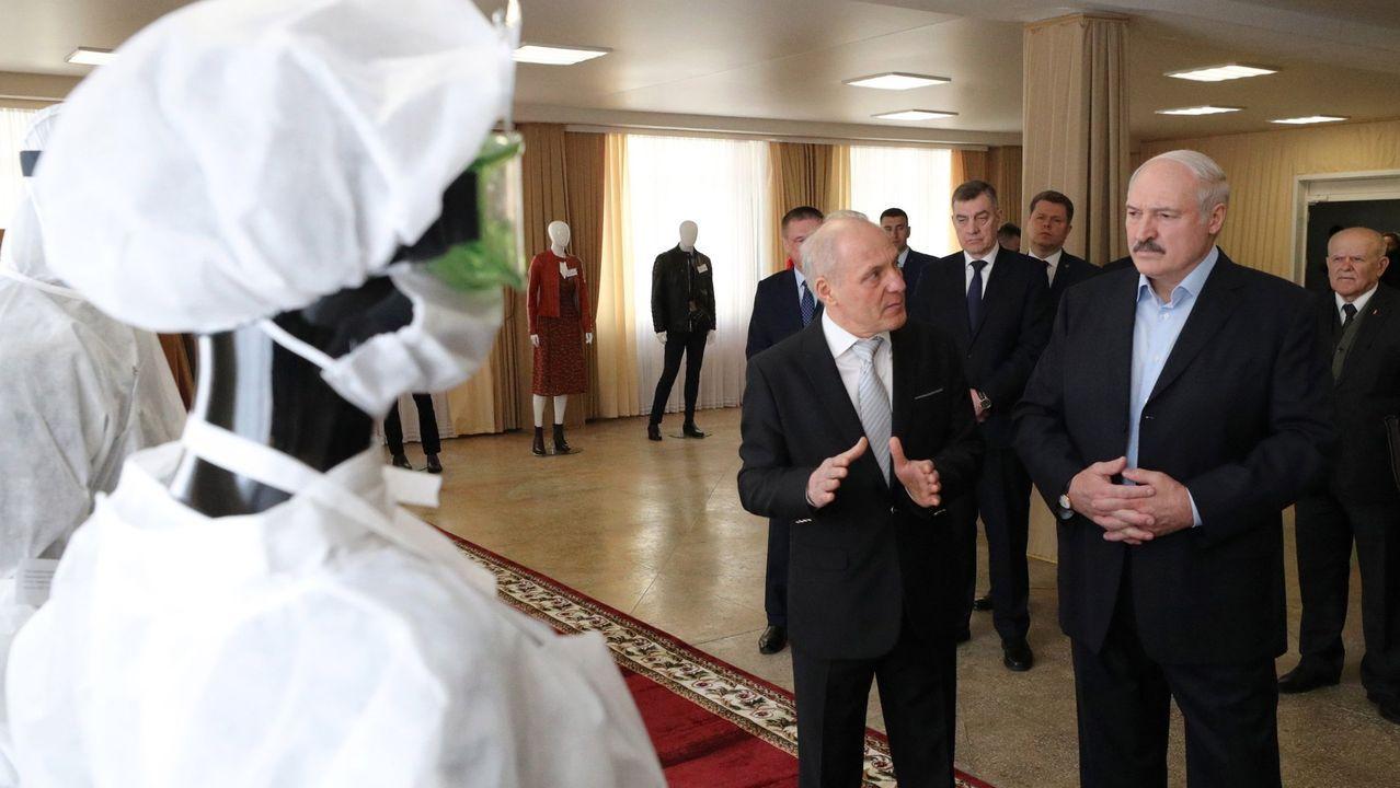 Amor, oración y homenajesa golpe de mascarilla.El presidente bielorruso, a la derecha, observa material sanitario
