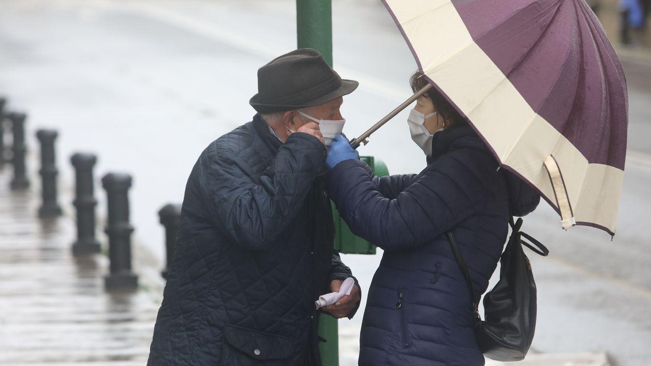 Gente mayor paseando bajo la lluvia en Santiago