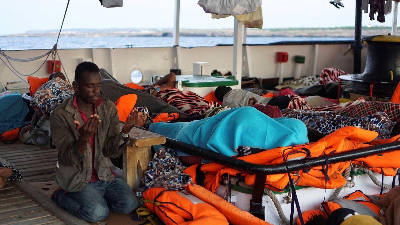 Dinero.Un migrante reza a primera hora de la mañana del lunes a bordo del Open Arms, fondeado frente a Lampedusa
