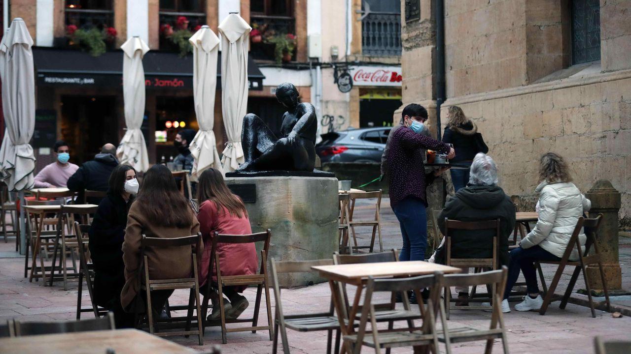La borrasca «Karim» desploma el techo del polideportivo de El Berrón.Varias personas consumen en una terraza en Oviedo