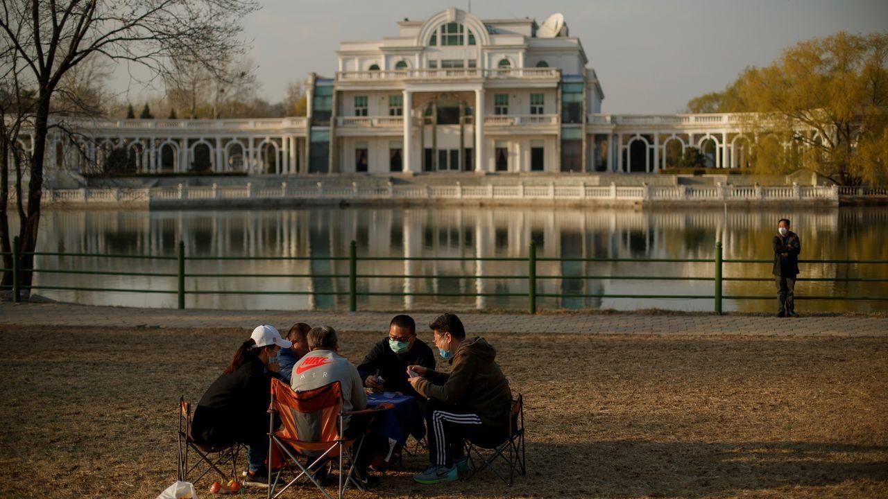 Ciudadanos chinos con mascarillas disfrutando del soleado sábado en Pekín