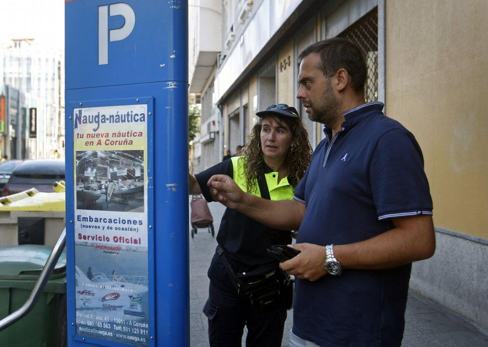 Una empleada de la ORA ayuda a un conductor a obtener su tique de aparcamiento.