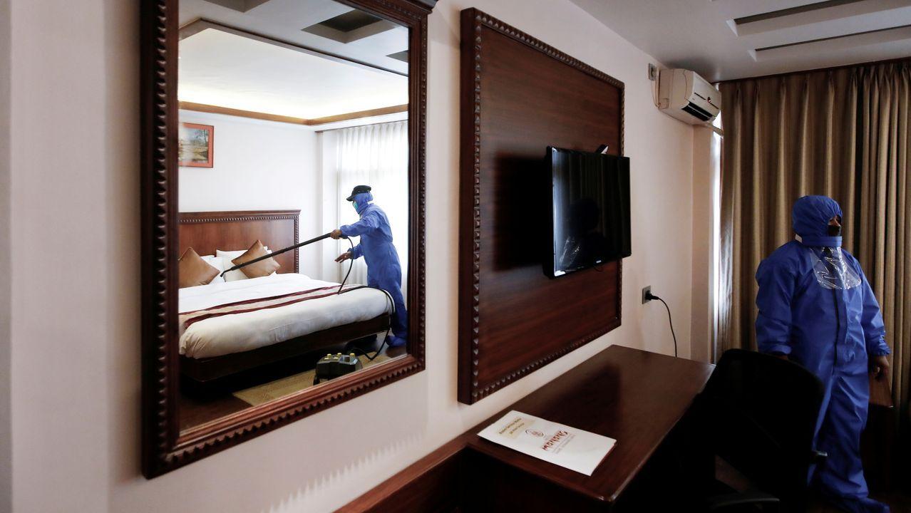 Dos empleados con trajes de protección desinfectan la habitación de un hotel en Nepal